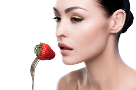 young woman eating strawberry on fork isolated on white