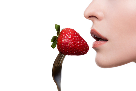 cropped shot of young woman eating strawberry on fork
