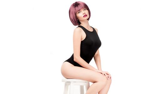 Jonge mooie vrouw in leotard poseren op stoel Stockfoto