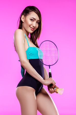 shuttlecock: young woman holding badminton racquet with shuttlecock and smiling at camera Stock Photo