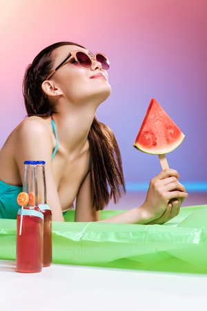 girl in sunglasses holding watermelon piece while sunbathing on swimming mattress