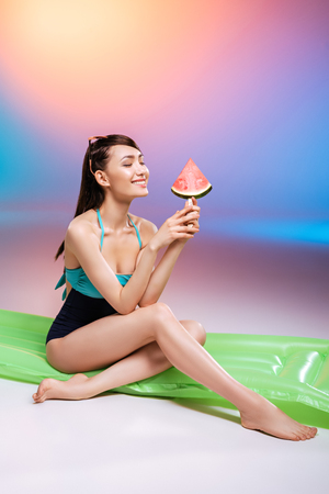 young woman in swimsuit sitting on swimming mattress and eating fresh juicy watermelon Banco de Imagens