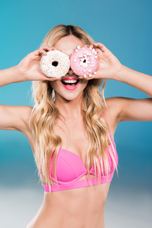 caucasian girl in swimsuit holding sweet doughnuts in front of face Stock Photo