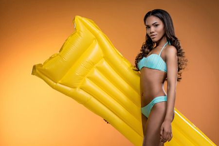 african american girl in swimwear posing with yellow swimming mattress Stok Fotoğraf