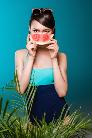 young asian woman in swimsuit holding watermelon piece in front of face Stock fotó