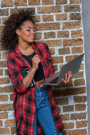 african american woman smiling while using laptop and holding notebooks Stock Photo