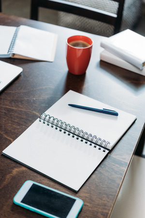 blank notebook with pen and smartphone with cup of coffee on tabletop