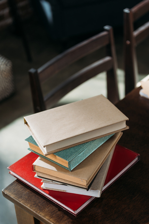 heap of books on wooden tabletop with copy space