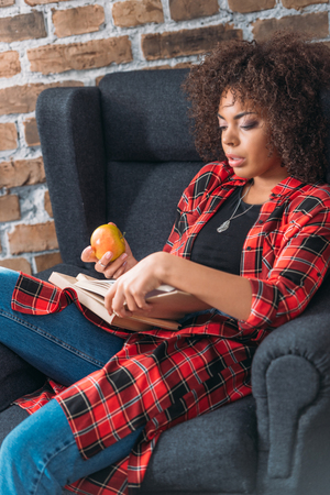 young woman sitting in chair and studying with books while eating apple