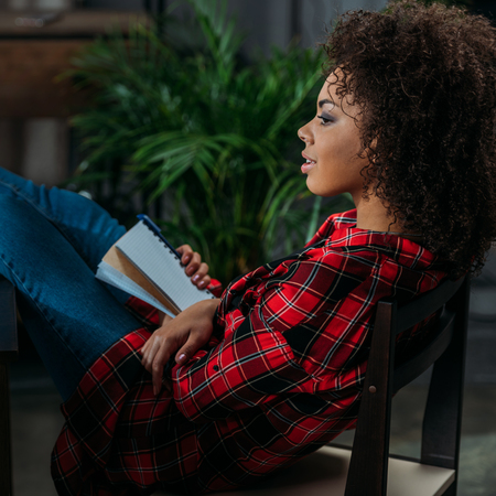african student: pensive young woman holding notebook with pen and looking away