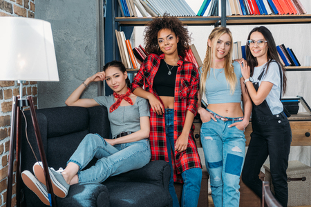 african student: stylish multiethnic women posing together at home library
