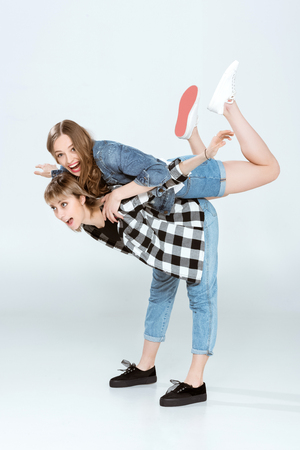 lesbian couple having fun and piggybacking isolated on grey
