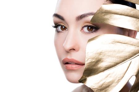 vrouw die gezicht behandelt met groot gouden blad dat op wit wordt geïsoleerd Stockfoto