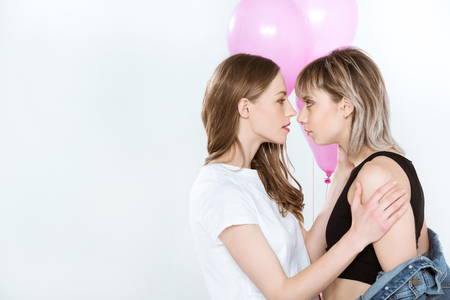 beautiful young lesbian couple holding pink balloons and looking at each other