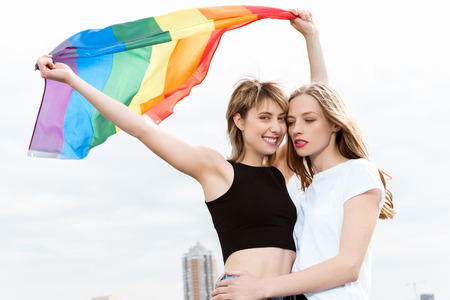 lesbian couple embracing and waving lgbt flag outdoors Stock Photo