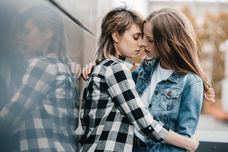 young lesbian couple hugging and kissing outdoors