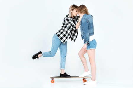 young homosexual couple standing on skateboard and kissing
