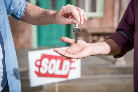 man buying new house and taking keys, sold sign behind