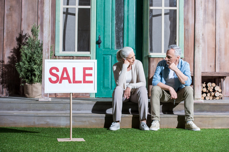 upset senior couple sitting on porch and selling their house Imagens