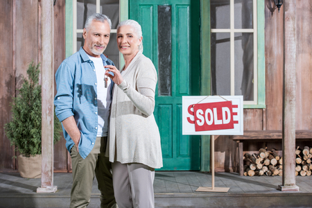 senior couple holding keys of their new house and standing on porch