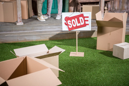 couple standing on porch of new house and sold sign with cardboard boxes on grass