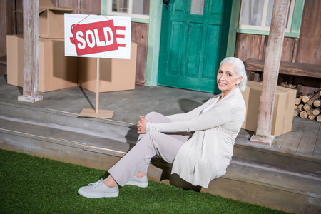 senior woman sitting on stairs of new house with sold sign 版權商用圖片