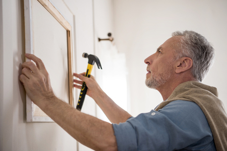 focused senior man hanging picture on wall at new home