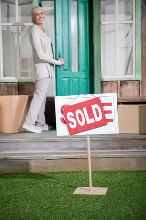 senior woman standing on porch of new house with sold sign