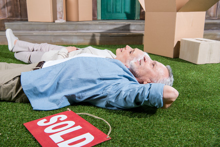 senior couple lying on green grass between cardboard boxes and sold sign Banco de Imagens