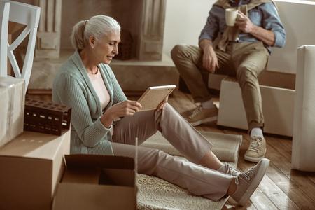 Esposa mirando una foto vieja mientras toma descanso de cajas de cartón de embalaje Foto de archivo - 82839534