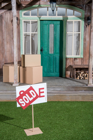 sign sold on green grass and cardboard boxes stacking on porch Фото со стока