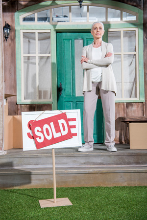senior woman with crossed arms standing on porch of new house and sold sign on green grass Фото со стока