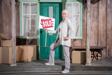 senior woman standing on stairs of new house and holding sold sign