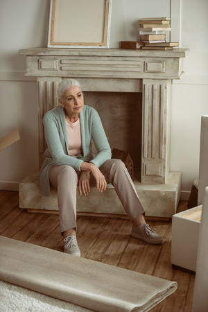 upset senior woman taking break from packing cardboard boxes