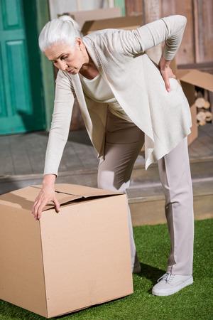 vrouw met rugpijn die zich op gras met grote kartondoos bevindt
