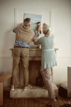 Marido y mujer altos colgando la imagen en la pared sobre la chimenea Foto de archivo - 82839562