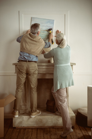 senior husband and wife hanging picture on wall over the fireplace