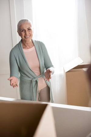 lachende senior vrouw dozen uitpakken en camera kijken