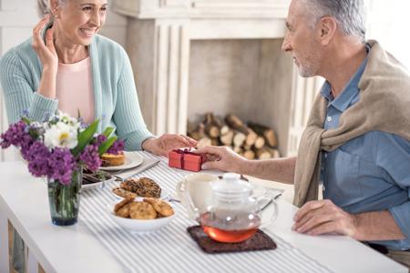haired mens die gift voorstelt aan zijn vrouw tijdens ontbijt thuis