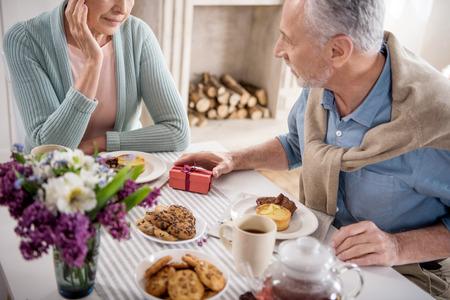 grijze haren man presenteert geschenk aan zijn vrouw tijdens het ontbijt