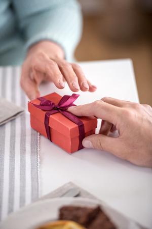 그의 아내에게 리본이 달린 상자에 선물을 제시하는 남자