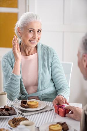 아침 식사 도중 웃는 아내에게 선물을 선물하는 남자 스톡 콘텐츠