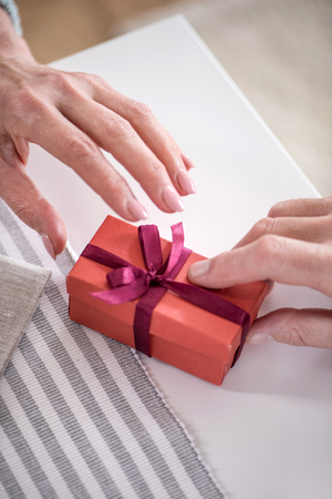 man presenting gift in box with ribbon to his wife Stock fotó