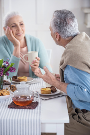 senior couple talking and having breakfast at home