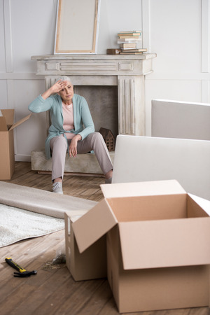 senior woman having rest on fireplace after unpacking boxes