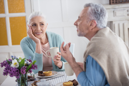 couple talking and drinking tea during breakfast at home Banco de Imagens