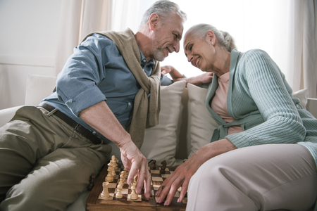 couple embracing while sitting at sofa and playing chess at home