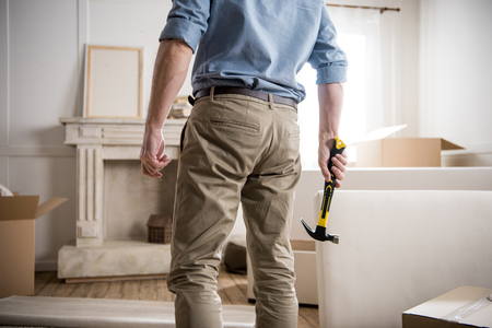 casual man with hammer standing in the room