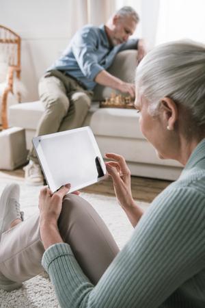 senior woman using digital tablet while her husband playing chess on sofa