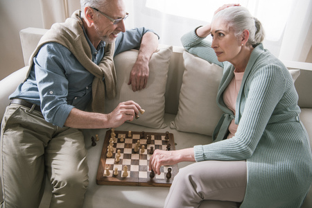 couple talking while playing chess on sofa at home